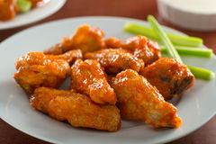 Spicy Chicken Wings with Sriracha Sauce. A plate of delicious spicy hot chicken wings with sriracha sauce and celery sticks Stock Photography