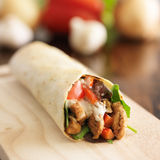 Spicy chicken wrap close up. Chicken wrap in tortilla with sauce and mesclun mix Royalty Free Stock Photography
