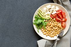 Spicy chickpeas, avocado, tomatoes, arugula bowl on dark background, top view. Delicious balanced food concept royalty free stock image