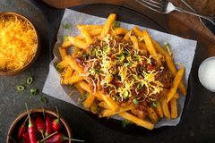 Spicy Chili Cheese Fries. Delicious homemade spicy chili fries with green onion and cheddar cheese Stock Photos