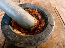 Spicy chili paste making on stone mortar Royalty Free Stock Image