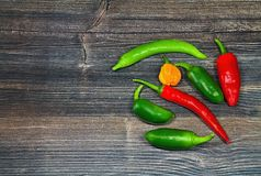 Spicy chili peppers on wooden board. Bunch of fresh chilli chilli peppers piled up together. The vegetable belongs botanically to the Genus Capsicum, being Royalty Free Stock Photo