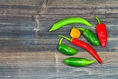 Spicy chili peppers on wooden board. Bunch of fresh chilli chilli peppers piled up together. The vegetable belongs botanically to the Genus Capsicum, being Stock Image