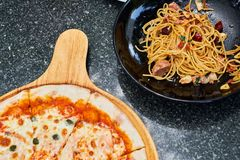Spicy and chili spaghetti in black dish and pizza serve on wood dish royalty free stock photo