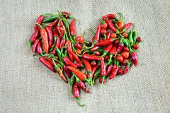 Spicy chilly peppers. Over burlap Stock Photos