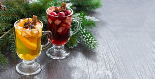 Spicy Christmas drinks in glasses on a wooden background Stock Photos