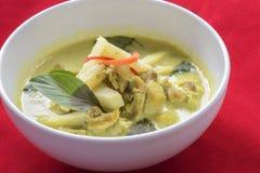Spicy ckhicken-curry in coconut milk. Spicy chicken-curry in coconut milk on red background Stock Photo