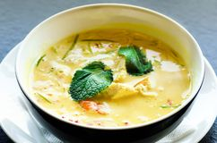 Spicy coconut milk cream soup curry with chiken, tiger prawns, long soy noodles, bean sprouts, lime, chilli pepper and. Mint. Asian traditional national cuisine royalty free stock photos