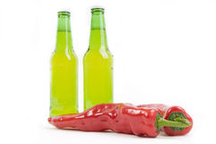 Spicy and cool. Two cool bottles of fine beer standing over two hot chili paprika's Stock Image