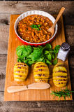 Spicy cowboy beans with hassleback potatoe with herbs Royalty Free Stock Photos