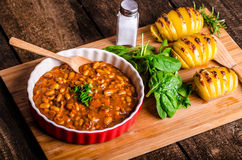 Spicy cowboy beans with hassleback potatoe with herbs Stock Photos