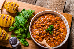 Spicy cowboy beans with hassleback potatoe with herbs Stock Photography