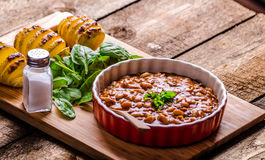Spicy cowboy beans with hassleback potatoe with herbs stock photo