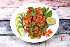 Spicy crispy deep-fried chicken salad. Thai recipe, Spicy crispy deep-fried chicken salad call Yum Kai Zap in Thai topped halve green lemon,cucumber and red Stock Image