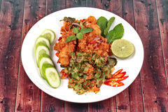 Spicy crispy deep-fried chicken salad. Thai recipe, Spicy crispy deep-fried chicken salad call Yum Kai Zap in Thai topped halve green lemon,cucumber and red Stock Photos