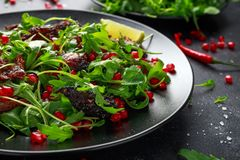 Spicy crispy duck salad with pomegranate seeds, lime and wild green rucola.  royalty free stock photos