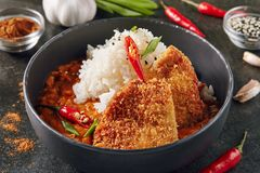 Spicy Crispy Fried Pork Fillet with Curry and Rice. Hot Spicy Crispy Fried Pork Fillet with Curry and Rice on Dark Background. Katsu or Tonkatsu with Red Peppres stock photo