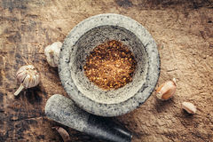 Spicy crushed peppers in a granite mortar. Stock Images