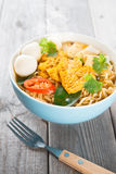 Spicy curry instant noodles soup. With fork on wooden dining table. Fresh cooked, hot with steamed smoke Royalty Free Stock Image