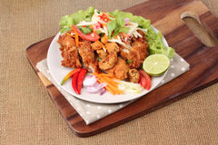 Spicy deep-fried chicken salad with roll green mango . Stock Image