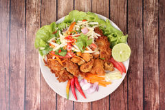 Spicy deep-fried chicken salad with roll green mango . Stock Photo