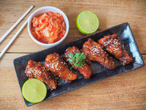 Spicy deep fried chicken wing. Korean style spicy sauce deep fried chicken wing serve with kimchi stock image