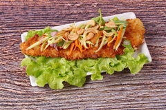 Spicy deep-fried Dolly`s fish salad with roll green mango. Royalty Free Stock Image
