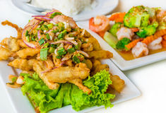 Spicy deep fried squid mingle serve with broccoli prawn salad. A Royalty Free Stock Photography