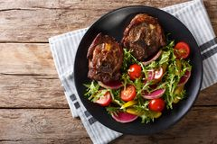 Spicy delicious lamb steak and salad from radish, tomatoes, pepp. Spicy delicious lamb steak and vegetable salad from radish, tomatoes, pepper and lettuce close Stock Image