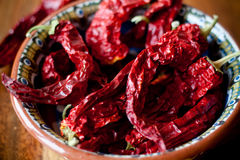 Spicy dried red peppers. In a clay dish on the table Stock Photos