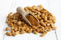 Spicy dry roasted peanuts on white with wood scoop. Stock Photos