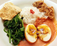 Spicy eggs Indonesian style. Homemade Indonesian dinner with eggs in spicy coconut and tomato sauce, spinach, rice, hot sauce, emping and rempeyek (peanut Royalty Free Stock Image