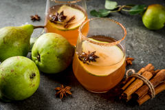 Spicy fall pear cocktail. Autumn drinks. Mulled wine. Traditional autumn spicy cocktail with pear, cider and chocolate syrup, with cinnamon, anise, brown sugar stock images