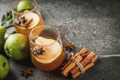 Spicy fall pear cocktail. Autumn drinks. Mulled wine. Traditional autumn spicy cocktail with pear, cider and chocolate syrup, with cinnamon, anise, brown sugar Royalty Free Stock Image