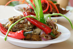 Spicy Fish. A plate of spicy fish cooked with herbs, onion and red chili, green chili as garnishing stock photo