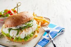 Spicy fish burger with rocket and mayonnaise stock photo