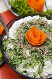 Spicy fish salad. A spicy fish and cucumber salad with onions and cut vegetable decorations royalty free stock image