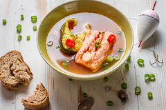 Spicy fish soup based on salmon. On old wooden table Royalty Free Stock Images