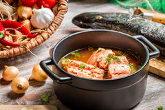 Spicy fish soup made ​​of salmon and spiced with dill. On old wooden table Royalty Free Stock Photo