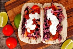 Spicy fish tacos downward view on wooden board. Two spicy fish tacos with red cabbage lime slaw, salsa and sour cream, downward view on wooden board stock photos