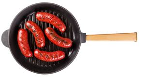 Spicy fragrant fried sausages in a cast-iron frying pan. Isolated on white background. The concept of traditional food Stock Photos