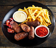 Spicy fried cevapcici rolled meat patties. Served with mayonnaise, tomato ketchup and golden French fries on a black plate, high angle square format stock images