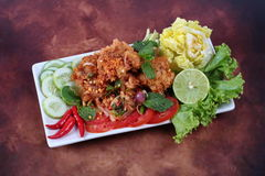 Spicy fried chicken salad (Yum Kai Zap in Thai) . Spicy fried chicken salad (Yum Kai Zap in Thai) as spicy chicken salad,chili,tomato,red onion,roasted rice Stock Photos