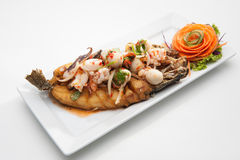 Spicy fried fish with seafood on top Stock Photo