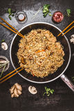 Spicy fried noodles in wok pan with chopsticks on dark rustic background, top view. Royalty Free Stock Photo