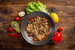Spicy fried rice with lamb on the black plate royalty free stock photography