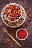 Spicy glazed almonds. Wood bowls filled with delicious spicy almond glazed honey, selective focus Stock Images
