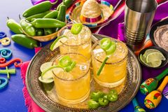 Spicy margarita. Spicy grapefruit margarita cocktail garnished with lime and jalapenos Royalty Free Stock Photos