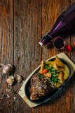 Spicy steak of the lamb chop iron pan. Food on dark wood background. Royalty Free Stock Photography