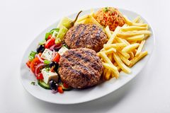 Spicy Greek bifteki meat balls. Served with a fresh salad, potato chips and tomato rice pilaf or domatorizo on an oval platter over white stock photos